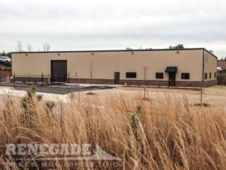 tan steel building with brown trim, brick wainscot, roll up doors