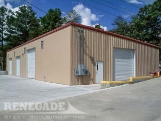 tan steel building with red roof trim, large white roll up doors, walk door