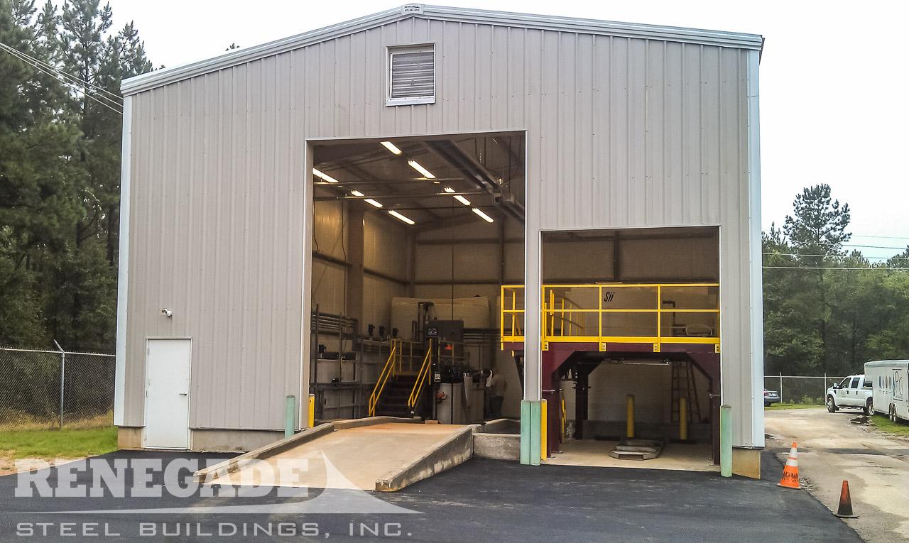 tan industrial steel metal building, white trim, large framed openings
