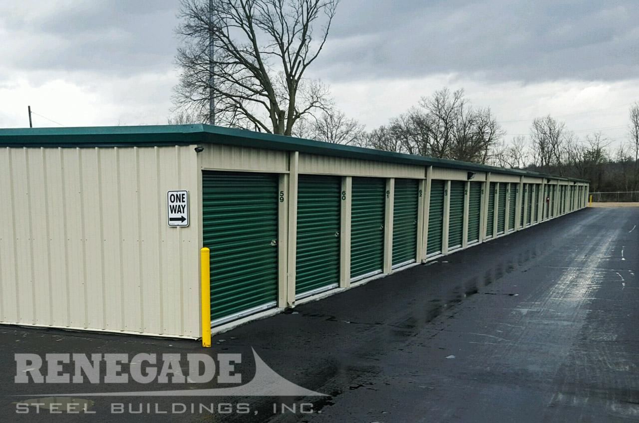 steel mini self storage tan building with green trim, green roll up doors, 8 units