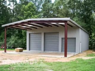 Gray steel building with gray trim, open front bay carport, large gray steel roll up doors