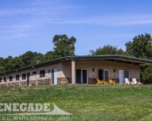 Tan steel building metal building with green trim, stone wainscot, sliding doors, windows, overhang and porch, open bay