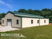 Tan steel metal building barn with raised green center roof, windows and door