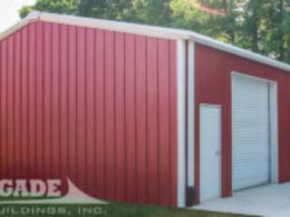 Red steel metal building, large white rollup door, white man door