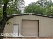 tan steel building with brown trim, large rollup door, walk door