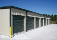 steel mini self storage tan building with green trim, roll up doors