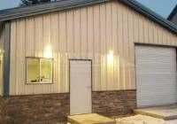 30x50x12 steel building with tan walls and green trim, walkdoor, windows, rollup doors and stone wainscot